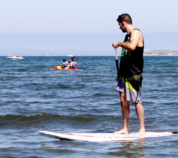 chico practicando paddle surf en la playa