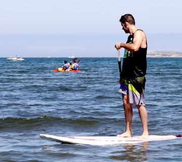 chico practicando paddle surf en la playa