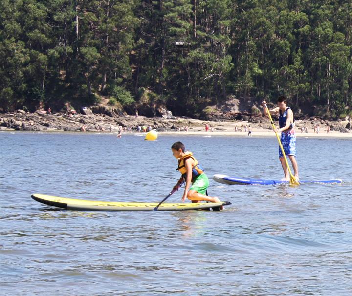 Niños practicando Paddle Surf en la playa