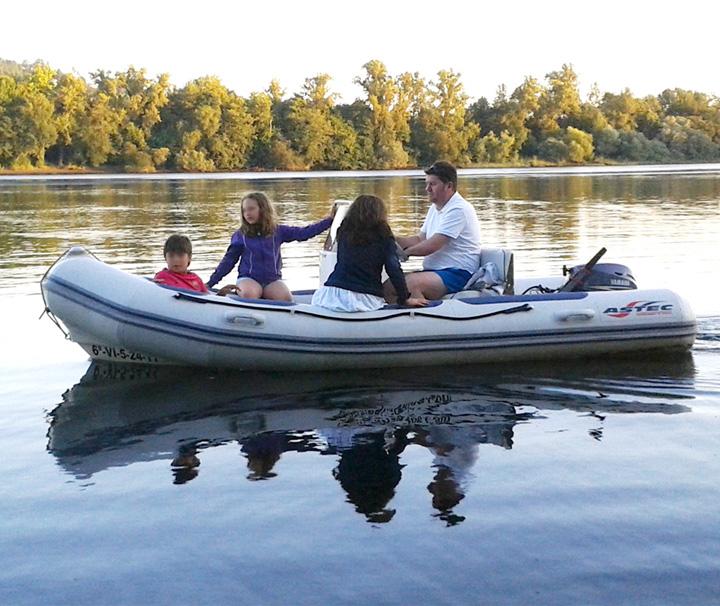 Familia navegando en lancha neumática por el Río Miño