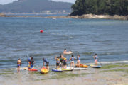 Grupo practicando paddle surf en la playa