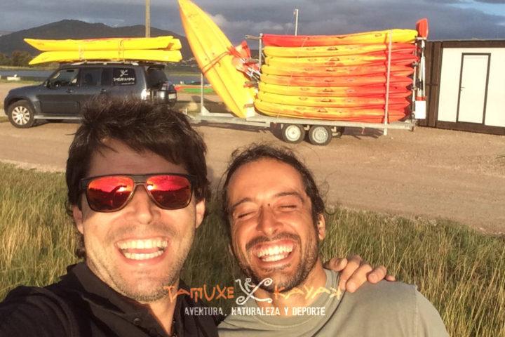 Amigos sonriendo delante de unos kayaks