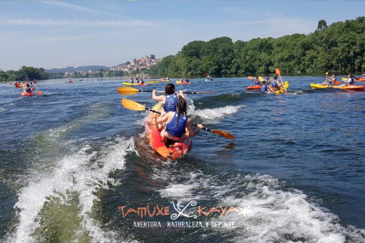 Grupo de kayaks biplaza navegando entre las olas