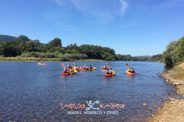 Grupo de kayaks acercándose a la orilla del río en Caldelas