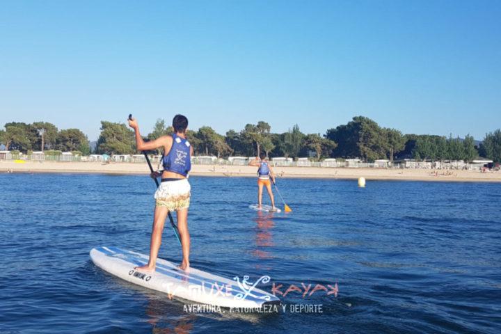 Niños practicando paddle surf en la playa de Ladeira