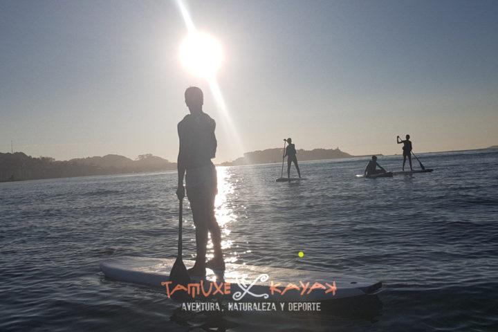 Grupo de amigos disfrutando del paddle surf en Baiona
